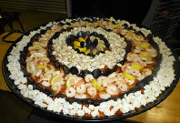 Photo of a large paella with a variety of meat and garnishes. Prepared by SMART Hospitality.